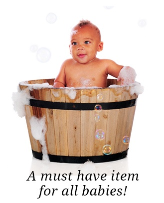 A baby sitting in a bath bucket.